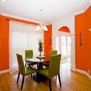 Foto di una sala da pranzo eclettica con pareti arancioni e pavimento in legno massello medio