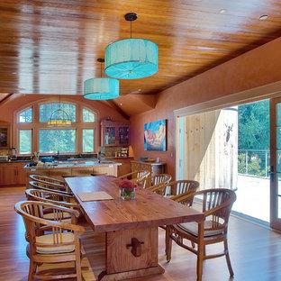 На фото: кухня-столовая среднего размера в стиле кантри с оранжевыми стенами и паркетным полом среднего тона без камина с