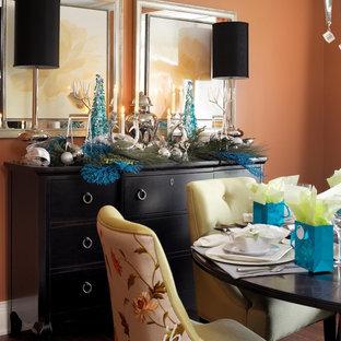 Cette photo montre une salle à manger chic de taille moyenne et fermée avec un mur orange et un sol en bois foncé.