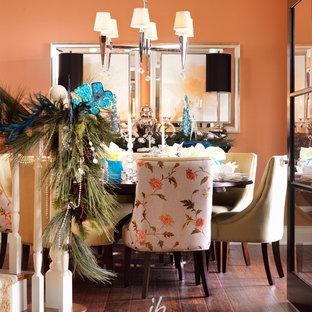 Réalisation d'une salle à manger tradition de taille moyenne et fermée avec un mur orange et un sol en bois foncé.