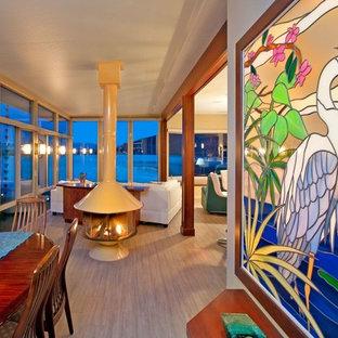Esempio di una sala da pranzo aperta verso il soggiorno chic con pareti beige, camino sospeso, cornice del camino in metallo e pavimento grigio