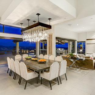 Foto di un'ampia sala da pranzo aperta verso il soggiorno minimalista con pareti bianche e pavimento in gres porcellanato
