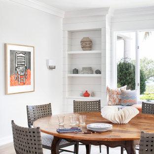 Exemple d'une salle à manger ouverte sur le salon bord de mer avec un mur blanc, un sol en bois brun, aucune cheminée, un sol marron et du lambris de bois.