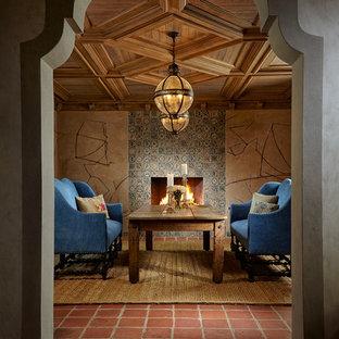 Immagine di una sala da pranzo mediterranea con pareti beige, camino classico, cornice del camino piastrellata e pavimento rosso