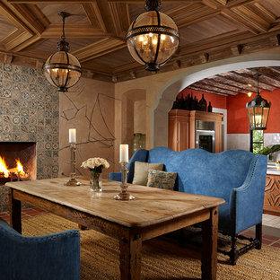 Foto di una sala da pranzo mediterranea con pareti beige, camino classico, cornice del camino piastrellata e pavimento rosso