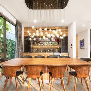 This is an example of a contemporary open plan dining in Melbourne with white walls, concrete floors, no fireplace and beige floor.