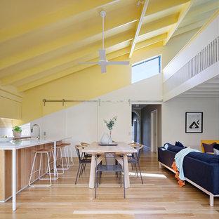 Exemple d'une salle à manger ouverte sur le salon tendance avec un mur blanc, un sol en bois brun et un sol marron.