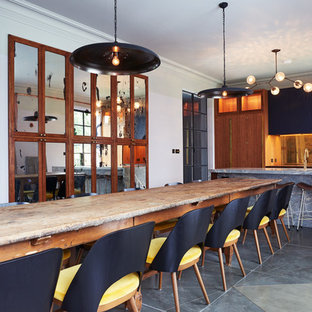 Photo of a contemporary kitchen/dining room in London with white walls, concrete flooring and grey floors.