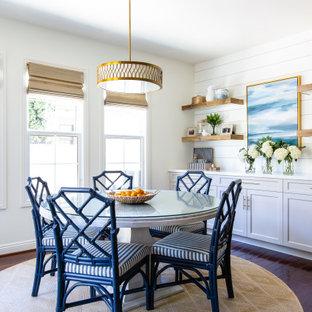Cette photo montre une salle à manger bord de mer de taille moyenne avec un mur blanc, un sol en bois foncé, un sol marron et du lambris de bois.