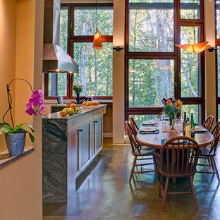 Immagine di una grande sala da pranzo aperta verso la cucina stile rurale con pareti gialle, pavimento in cemento, camino bifacciale, cornice del camino piastrellata e pavimento multicolore
