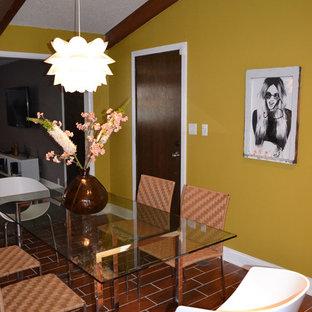 Große Mid-Century Wohnküche mit gelber Wandfarbe, Backsteinboden, Kamin, Kaminsims aus Metall und braunem Boden in Kansas City