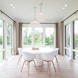 Réalisation d'une grande salle à manger nordique fermée avec un mur blanc et un sol en bois clair.