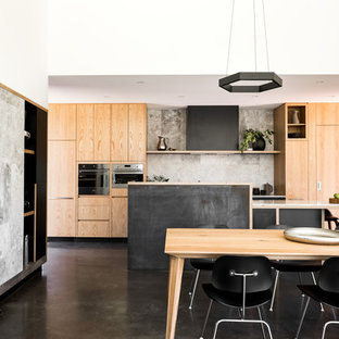 Modern kitchen/dining combo in Perth with white walls, concrete floors and black floor.