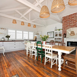 Tropical dining room in Brisbane with white walls, dark hardwood floors, a standard fireplace, brown floor and vaulted.