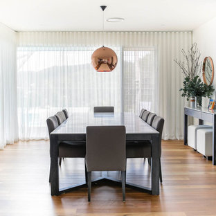 Design ideas for a contemporary separate dining room in Newcastle - Maitland with white walls, medium hardwood floors and brown floor.