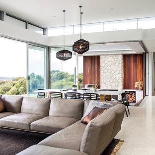 Imagen de comedor moderno, grande, abierto, con paredes blancas, suelo de cemento, chimenea de esquina y marco de chimenea de metal