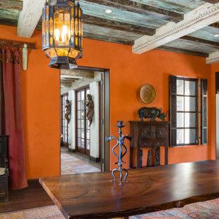 Immagine di una grande sala da pranzo aperta verso il soggiorno mediterranea con pareti arancioni, parquet scuro, camino classico, cornice del camino in pietra e pavimento marrone
