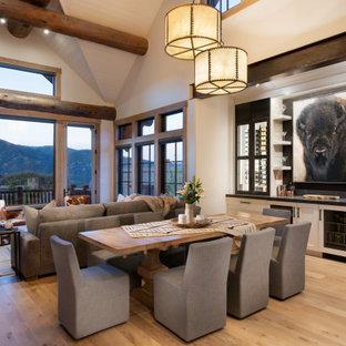 Idée de décoration pour une salle à manger ouverte sur le salon chalet de taille moyenne avec un mur blanc, un sol en bois brun, un sol marron et un plafond voûté.
