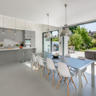 This is an example of a contemporary kitchen/dining room in London with beige walls, concrete flooring and grey floors.