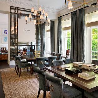 На фото: огромная гостиная-столовая в классическом стиле с белыми стенами, темным паркетным полом, двусторонним камином и фасадом камина из металла
