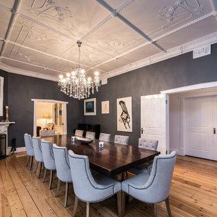Foto di una grande sala da pranzo chic chiusa con pareti grigie, pavimento in legno massello medio, camino ad angolo, cornice del camino in legno e pavimento marrone