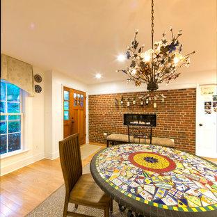 Ispirazione per una sala da pranzo aperta verso il soggiorno american style di medie dimensioni con pareti bianche, parquet chiaro, camino lineare Ribbon e cornice del camino in mattoni