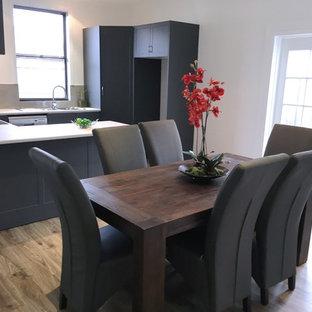 Esempio di una sala da pranzo aperta verso la cucina minimal di medie dimensioni con pareti bianche, pavimento in laminato e pavimento marrone