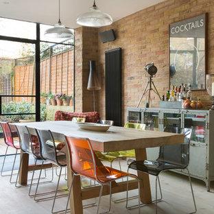 Immagine di una sala da pranzo boho chic con pareti arancioni, parquet chiaro e pavimento beige