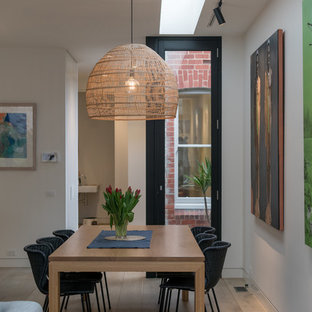 Inspiration for a contemporary open plan dining in Melbourne with white walls, medium hardwood floors and brown floor.