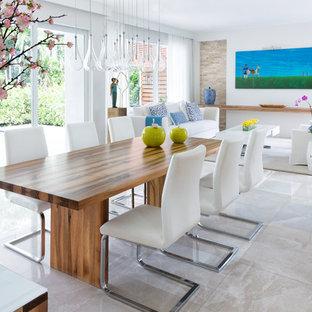 Réalisation d'une grand salle à manger ouverte sur le salon marine avec un mur gris, un sol en marbre, aucune cheminée et un sol beige.