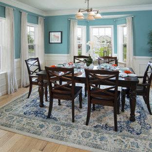 Foto di una sala da pranzo chic chiusa e di medie dimensioni con pareti blu e parquet chiaro