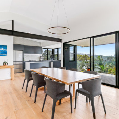 Example of a trendy medium tone wood floor and brown floor great room design in Central Coast with white walls and no fireplace