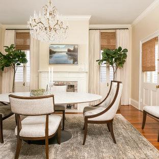 Ispirazione per una sala da pranzo chic chiusa e di medie dimensioni con pareti beige, pavimento in legno massello medio, camino classico, cornice del camino in mattoni e pavimento marrone