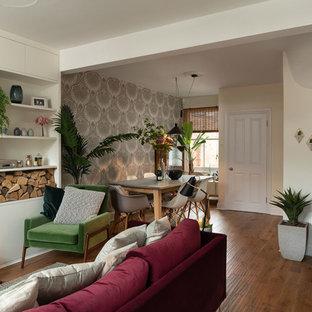 Imagen de comedor ecléctico, de tamaño medio, abierto, con paredes beige, suelo de madera en tonos medios, estufa de leña y marco de chimenea de hormigón