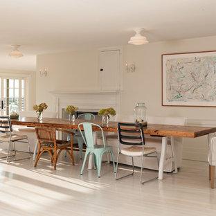 Foto di una grande sala da pranzo aperta verso la cucina country con pareti bianche, camino classico, cornice del camino in intonaco, parquet chiaro e pavimento bianco