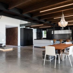 Esempio di una grande sala da pranzo aperta verso il soggiorno minimal con pareti bianche, pavimento in cemento, camino lineare Ribbon, cornice del camino in cemento e pavimento grigio
