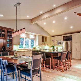 Diseño de comedor de cocina de estilo americano, de tamaño medio, con paredes beige, suelo de madera clara, chimenea de doble cara y marco de chimenea de piedra