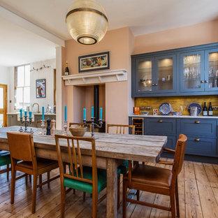 Diseño de comedor de cocina ecléctico, grande, con suelo de madera en tonos medios, parades naranjas, estufa de leña y suelo marrón