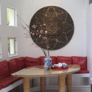 Cette photo montre une petit salle à manger ouverte sur la cuisine tendance avec un mur blanc, un sol en calcaire et un sol beige.