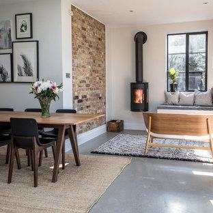 Inredning av en modern mellanstor separat matplats, med vita väggar, betonggolv, en öppen vedspis, en spiselkrans i metall och grått golv