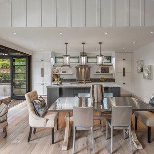 Immagine di una sala da pranzo aperta verso la cucina country di medie dimensioni con pareti bianche, parquet chiaro, nessun camino e pavimento beige