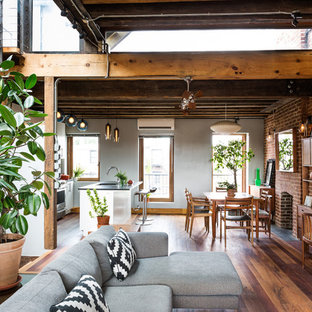 Inspiration for an industrial medium tone wood floor kitchen/dining room combo remodel in New York with a standard fireplace and a brick fireplace