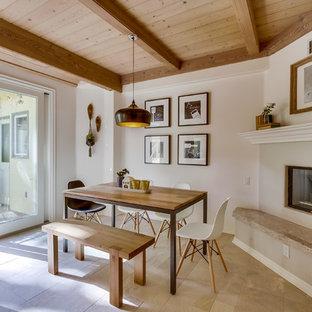 サンディエゴの中サイズの北欧スタイルのおしゃれな独立型ダイニング (セラミックタイルの床、白い壁、コーナー設置型暖炉、漆喰の暖炉まわり) の写真