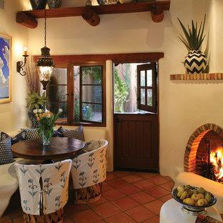 Modelo de comedor de estilo americano con paredes beige, chimenea de esquina y suelo de baldosas de terracota
