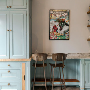 This is an example of a small traditional kitchen/dining room in London with grey walls, light hardwood flooring and brown floors.
