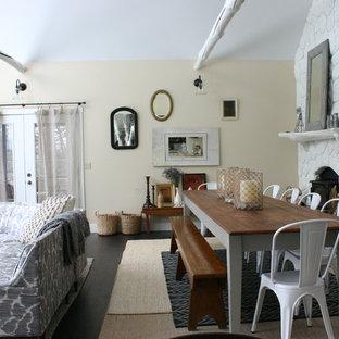Réalisation d'une salle à manger style shabby chic avec un mur beige, un sol en bois foncé et un manteau de cheminée en pierre.
