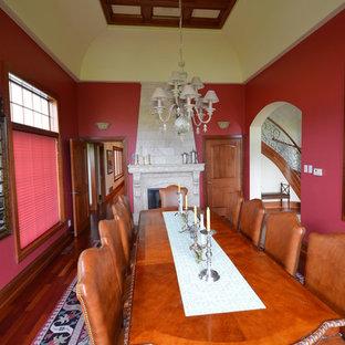 Idee per una sala da pranzo chic di medie dimensioni e chiusa con pareti rosse, parquet scuro, camino classico e cornice del camino in pietra