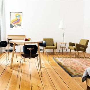 Kleines Mid-Century Esszimmer ohne Kamin mit weißer Wandfarbe und braunem Holzboden in Berlin