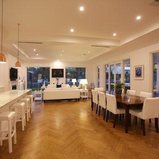 Foto de comedor de cocina marinero, grande, con paredes blancas, suelo de madera en tonos medios, chimenea tradicional y marco de chimenea de madera