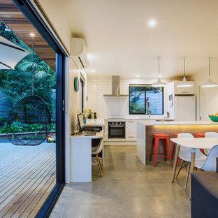 Inspiration för ett litet funkis kök med matplats, med vita väggar och betonggolv